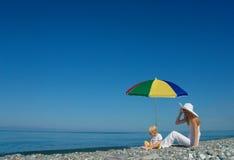 Frau und Kind sitzen unter einem Regenschirm Stockfotos