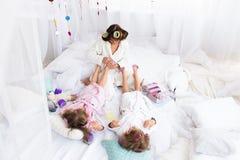 Frau und Kinder auf Bett Lizenzfreies Stockbild