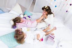 Frau und Kinder auf Bett Stockbild