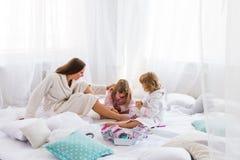 Frau und Kinder auf Bett Stockbilder