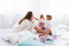 Frau und Kinder auf Bett Stockfotos