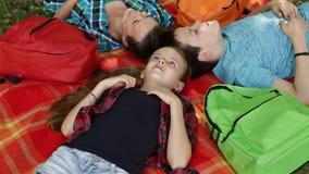 Frau und Kinder auf einem Picknick, das auf Decke sich entspannt und liegt stock footage