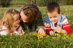 Frau und Kinder, die auf der Frühlingswiese sich entspannen Lizenzfreie Stockbilder