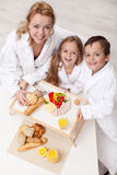 Frau und Kinder, die ein Licht und einen gesunden Snack essen Stockbild