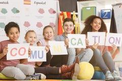 Frau und Kinder, die Kommunikationsaufschrift halten Stockfotografie