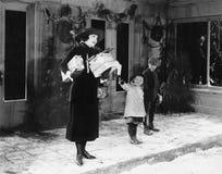 Frau und Kinder draußen mit Weihnachtsgeschenken (alle dargestellten Personen sind nicht längeres lebendes und kein Zustand exist Stockbild