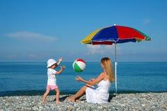 Frau und Kinderspiel eine Kugel an der Küste Lizenzfreies Stockbild