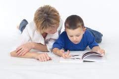 Frau und kleiner Junge, die Buch sehen Stockbild