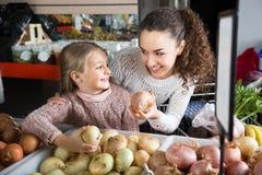 Frau und kleines blondes Mädchen, die whith Zwiebeln in Abteilung f aufwerfen Lizenzfreies Stockbild