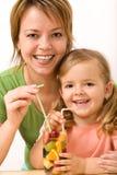Frau und kleines Mädchen, die eine fruchtige Erfrischung essen lizenzfreie stockfotografie