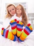 Frau und kleines Mädchen, die lustige Socken tragen Lizenzfreie Stockfotografie
