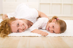 Frau und kleines Mädchen, die Spaß auf dem Fußboden haben lizenzfreie stockfotografie