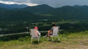 Frau und kleines Mädchen sitzen auf Berg stock video