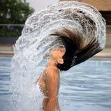 Frau und Lichtbogen des Wassers im Pool Stockfotografie