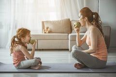 Frau und Mädchen betrachten einander und das Essen stockfotografie