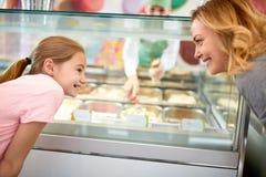 Frau und Mädchen, die über Auswahl der Eiscreme sich beraten stockfoto