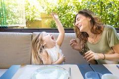 Frau und Mädchen, die heraus lautes im Restaurant lachen Lizenzfreie Stockfotos