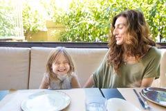 Frau und Mädchen, die mit lustigem Ausdruck im Restaurant lachen Lizenzfreie Stockfotografie