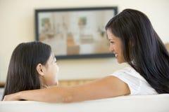 Frau und Mädchen im Raum mit Fernsehen des flachen Bildschirms Lizenzfreies Stockfoto