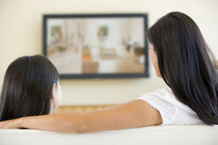 Frau und Mädchen im Raum mit Fernsehen des flachen Bildschirms Stockfotografie
