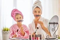 Frau und Mädchen mit dem Schnurrbart auf Stöcken Stockfotografie