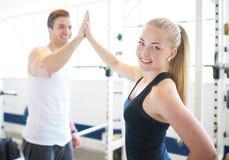 Frau und Mann in der Turnhalle feiernd mit Hoch fünf Lizenzfreie Stockfotos