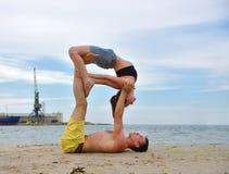 Frau und Mann, die akrobatisches Yoga tun Lizenzfreies Stockbild