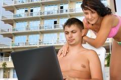 Frau und Mann, die auf Wagenaufenthaltsräume auf Strand stützen Stockfoto