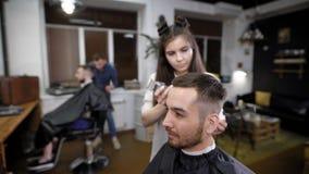 Frau und Mann, die den männlichen Kunden im Salon klassisches stilvolles Haar herstellen stock footage