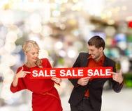 Frau und Mann, die Finger auf rotes Verkaufszeichen zeigen Lizenzfreies Stockfoto