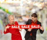 Frau und Mann, die Finger auf rotes Verkaufszeichen zeigen Lizenzfreies Stockbild