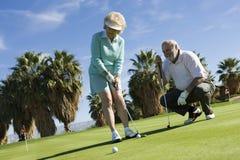 Frau und Mann, die Golf spielen lizenzfreies stockfoto