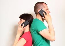 Frau und Mann, die am Handy sprechen Lizenzfreie Stockfotografie