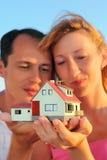 Frau und Mann, die im Handbaumuster des Hauses halten Lizenzfreies Stockfoto