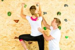 Frau und Mann, die an steigender Wand steigen Stockbild