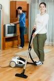 Frau und Mann, die zusammen Hausarbeit im Haus tun Stockbild