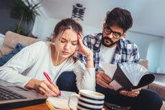 Frau und Mann, die zusammen Schreibarbeit, Steuern online zahlend tut lizenzfreie stockfotografie