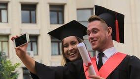 Frau und Mann graduiert in den akademischen Kleidern und in den Kappen, die Video am Telefon schießen stock video