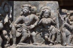 Frau und Mann im Trachtenmodetanzen auf Entlastung des des 12. Jahrhundertshoysaleshwara-Tempels in Halebidu, Indien Stockbild