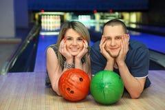 Frau und Mann liegen längsseits im Bowlingspielklumpen Lizenzfreies Stockbild