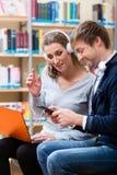 Frau und Mann mit Laptop und Telefon in der Bibliothek Stockfoto