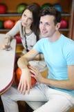 Frau und Mann sitzen am Tisch im Bowlingspielklumpen Lizenzfreie Stockbilder