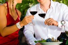 Frau und Mann in trinkendem Wein des Weinbergs Lizenzfreies Stockbild