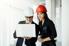 Frau und Mannunternehmer und -architekt im hemlet beim Geschäftstreffen, den Laptop auf Bauplänen betrachtend stockfoto