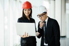 Frau und Mannunternehmer und -architekt im hemlet beim Geschäftstreffen, den Laptop auf Bauplänen betrachtend lizenzfreies stockbild