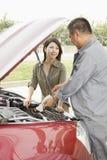 Frau und Mechaniker Working auf Auto Lizenzfreie Stockfotografie