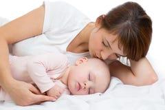 Frau und neugeborener Junge entspannen sich in einem weißen Schlafzimmer Junge Mutter, die ihr neugeborenes Kind küsst Mutterkran lizenzfreie stockbilder