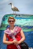 Frau und Seemöwe in einem Hafen stockfotos