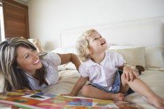 Frau und Sohn mit Buch im Bett Stockfoto