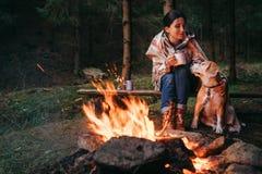 Frau und Spürhund verfolgen warmes nahe dem Lagerfeuer lizenzfreie stockbilder